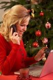 Γυναίκα που ψωνίζει on-line για τα δώρα Χριστουγέννων στο τηλέφωνο Στοκ φωτογραφία με δικαίωμα ελεύθερης χρήσης