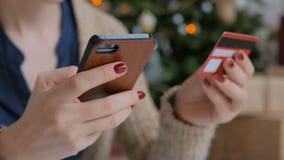 Γυναίκα που ψωνίζει on-line και που χρησιμοποιεί το smartphone με την πιστωτική κάρτα απόθεμα βίντεο