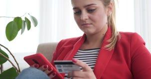 Γυναίκα που ψωνίζει on-line με το κινητό τηλέφωνο και την πιστωτική κάρτα απόθεμα βίντεο