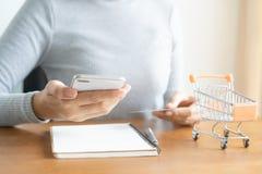 Γυναίκα που ψωνίζει on-line στο κάρρο Χέρι επιχειρησιακών γυναικών χρησιμοποιώντας το έξυπνο τηλέφωνο, πληρωμές και κρατώντας τις στοκ φωτογραφία
