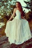 Γυναίκα πολυτέλειας σε ένα δάσος σε ένα μακρύ εκλεκτής ποιότητας φόρεμα κοντά στη λίμνη Στοκ Φωτογραφίες