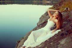 Γυναίκα πολυτέλειας σε ένα δάσος σε ένα μακρύ εκλεκτής ποιότητας φόρεμα κοντά στη λίμνη Στοκ Εικόνα