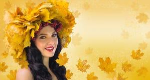 Γυναίκα-πτώση Όμορφη γυναίκα στο στεφάνι των φύλλων φθινοπώρου και gueld Στοκ φωτογραφία με δικαίωμα ελεύθερης χρήσης