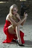 Γυναίκα πυροβόλων όπλων στο κόκκινο φόρεμα στοκ εικόνα με δικαίωμα ελεύθερης χρήσης
