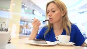 Γυναίκα σε έναν καφέ κατανάλωσης καφέδων με το κέικ σοκολάτας φιλμ μικρού μήκους