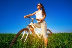 Γυναίκα σε έναν πράσινο τομέα σε ένα ποδήλατο Στοκ φωτογραφία με δικαίωμα ελεύθερης χρήσης