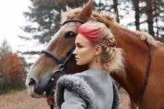 Γυναίκα σε ένα άλογο το φθινόπωρο Δημιουργικό φωτεινό ρόδινο makeup στο πρόσωπο κοριτσιών, χρωματισμός τρίχας Πορτρέτο ενός κοριτ στοκ εικόνες