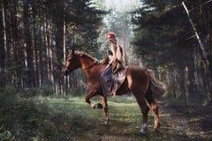 Γυναίκα σε ένα άλογο το φθινόπωρο Δημιουργικό φωτεινό ρόδινο makeup στο πρόσωπο κοριτσιών, χρωματισμός τρίχας Πορτρέτο ενός κοριτ στοκ εικόνα