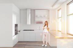 Γυναίκα σε ένα άσπρο μινιμαλιστικό εσωτερικό κουζινών στοκ εικόνα με δικαίωμα ελεύθερης χρήσης