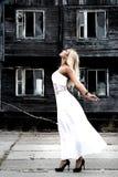 Γυναίκα σε ένα άσπρο φόρεμα στο υπόβαθρο του παλαιού σπιτιού Στοκ φωτογραφίες με δικαίωμα ελεύθερης χρήσης