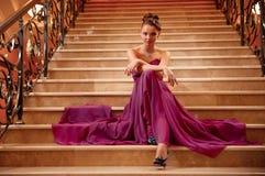 Γυναίκα σε ένα μακρύ φόρεμα που βρίσκεται στα σκαλοπάτια Στοκ Φωτογραφίες