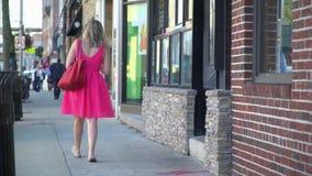 Γυναίκα σε ένα φωτεινό ρόδινο φόρεμα που περπατά κάτω από ένα πεζοδρόμιο απόθεμα βίντεο