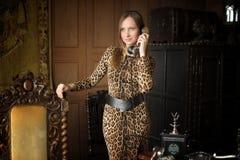 Γυναίκα σε ένα φόρεμα τυπωμένων υλών λεοπαρδάλεων με το αναδρομικό γραφείο στοκ εικόνες