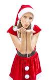 Γυναίκα σε ένα φόρεμα Χριστουγέννων που φυσά ένα φιλί σε σας Στοκ Φωτογραφία