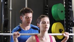 Γυναίκα σε βάρη ανύψωσης γυμναστικής στο φραγμό απόθεμα βίντεο