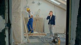 Γυναίκα σε μια κλήση με τους αναδόχους που συζητούν στο εργοτάξιο οικοδομής φιλμ μικρού μήκους
