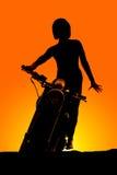 Γυναίκα σκιαγραφιών σε ετοιμότητα μπροστινό στάσεων μοτοσικλετών κάτω Στοκ Εικόνες