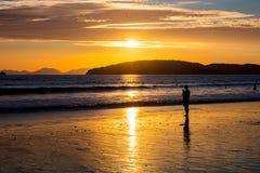 Γυναίκα σκιαγραφιών στην παραλία κατά τη διάρκεια του ηλιοβασιλέματος Στοκ Εικόνες