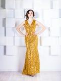Γυναίκα σούπερ σταρ που φορά το χρυσό λάμποντας φόρεμα στοκ φωτογραφία