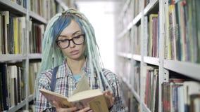 Γυναίκα σπουδαστής Hipster studiyng σκληρά στη βιβλιοθήκη φιλμ μικρού μήκους