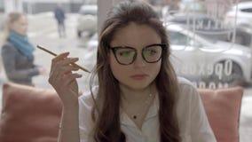 Γυναίκα σπουδαστών που σκέφτεται σκληρά να εργαστεί στον καφέ και την κατανάλωση του καφέ, 4K απόθεμα βίντεο