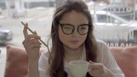 Γυναίκα σπουδαστών που σκέφτεται σκληρά να εργαστεί στον καφέ με το lap-top φιλμ μικρού μήκους