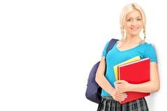 Γυναίκα σπουδαστής με τα βιβλία εκμετάλλευσης σχολικών τσαντών και κλίση ενάντια Στοκ φωτογραφίες με δικαίωμα ελεύθερης χρήσης
