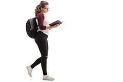 Γυναίκα σπουδαστής με το σακίδιο πλάτης που περπατά και που διαβάζει το βιβλίο Στοκ Εικόνα
