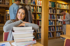 Γυναίκα σπουδαστής με το σωρό των βιβλίων ενώ άλλα στο υπόβαθρο στη βιβλιοθήκη Στοκ Φωτογραφίες