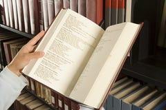 Γυναίκα σπουδαστής που διαβάζει ένα βιβλίο στη βιβλιοθήκη Στοκ Εικόνες