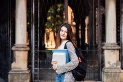 Γυναίκα σπουδαστής που κρατά ένα σημειωματάριο και που χαμογελά υπαίθρια κοντά σε Uni Στοκ Εικόνες
