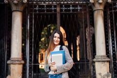 Γυναίκα σπουδαστής που κρατά ένα σημειωματάριο και που χαμογελά υπαίθρια κοντά σε Uni Στοκ φωτογραφία με δικαίωμα ελεύθερης χρήσης