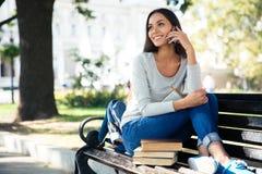 Γυναίκα σπουδαστής που μιλά στο τηλέφωνο υπαίθρια Στοκ Εικόνες