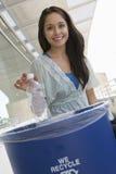 Γυναίκα σπουδαστής που ρίχνει το πλαστικό μπουκάλι στο σκουπιδοτενεκές Στοκ εικόνα με δικαίωμα ελεύθερης χρήσης