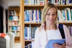 Γυναίκα σπουδαστής που χρησιμοποιεί την ταμπλέτα στη βιβλιοθήκη στοκ φωτογραφία με δικαίωμα ελεύθερης χρήσης