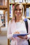 Γυναίκα σπουδαστής που χρησιμοποιεί την ταμπλέτα στη βιβλιοθήκη στοκ φωτογραφίες