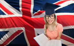 Γυναίκα σπουδαστών στο mortarboard πέρα από την αγγλική σημαία Στοκ Φωτογραφία