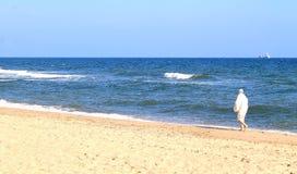 Γυναίκα στα άσπρα ενδύματα στην παραλία Στοκ εικόνα με δικαίωμα ελεύθερης χρήσης