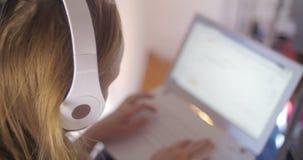 Γυναίκα στα ακουστικά που χρησιμοποιούν το lap-top απόθεμα βίντεο