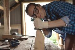 Γυναίκα στα γυαλιά ασφάλειας που λειτουργούν τη μηχανή πλανίσματος στην ξύλινη μπροστινή άποψη πινάκων Στοκ Εικόνες