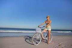 Γυναίκα στα γυαλιά ηλίου που κάθεται στο ποδήλατο στην παραλία στην ηλιοφάνεια στοκ εικόνες