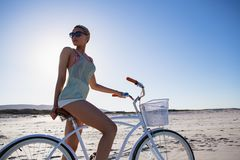 Γυναίκα στα γυαλιά ηλίου που κάθεται στο ποδήλατο στην παραλία στην ηλιοφάνεια στοκ φωτογραφία