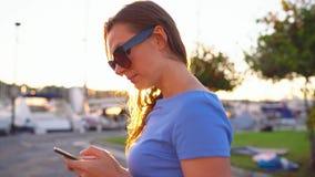 Γυναίκα στα γυαλιά ηλίου που χρησιμοποιούν το smartphone περπατώντας κάτω από μια αποβάθρα με πολλές γιοτ και βάρκες στο ηλιοβασί φιλμ μικρού μήκους