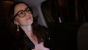 Γυναίκα στα γυαλιά που εξετάζει το κινητό τηλέφωνο ενώ στο κάθισμα επιβατών Κορίτσι με πρωταγωνιστή στην οθόνη smartphone της ενώ απόθεμα βίντεο