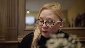 Γυναίκα στα γυαλιά που κάθονται σε έναν καφέ και που περιμένουν την άφιξη του σερβιτόρου Κινηματογράφηση σε πρώτο πλάνο του προσώ φιλμ μικρού μήκους