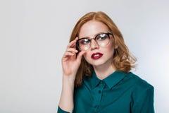 Γυναίκα στα γυαλιά, γυναίκα σε ένα άσπρο υπόβαθρο Όμορφη redhead επιχειρησιακή γυναίκα Στοκ Φωτογραφία
