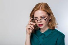Γυναίκα στα γυαλιά, γυναίκα σε ένα άσπρο υπόβαθρο Όμορφη redhead επιχειρησιακή γυναίκα Στοκ Φωτογραφίες