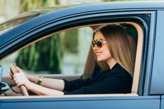 Γυναίκα στα γυαλιά ηλίου πίσω από τη ρόδα Στοκ Φωτογραφίες