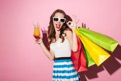 Γυναίκα στα γυαλιά ηλίου που πίνουν το κοκτέιλ και που κρατούν τις ζωηρόχρωμες τσάντες αγορών Στοκ Φωτογραφία