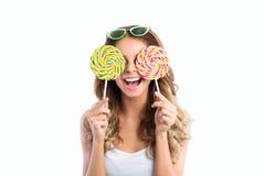 Γυναίκα στα γυαλιά ηλίου που χαμογελούν και που κρατούν δύο μεγάλα lollipops Στοκ Φωτογραφίες